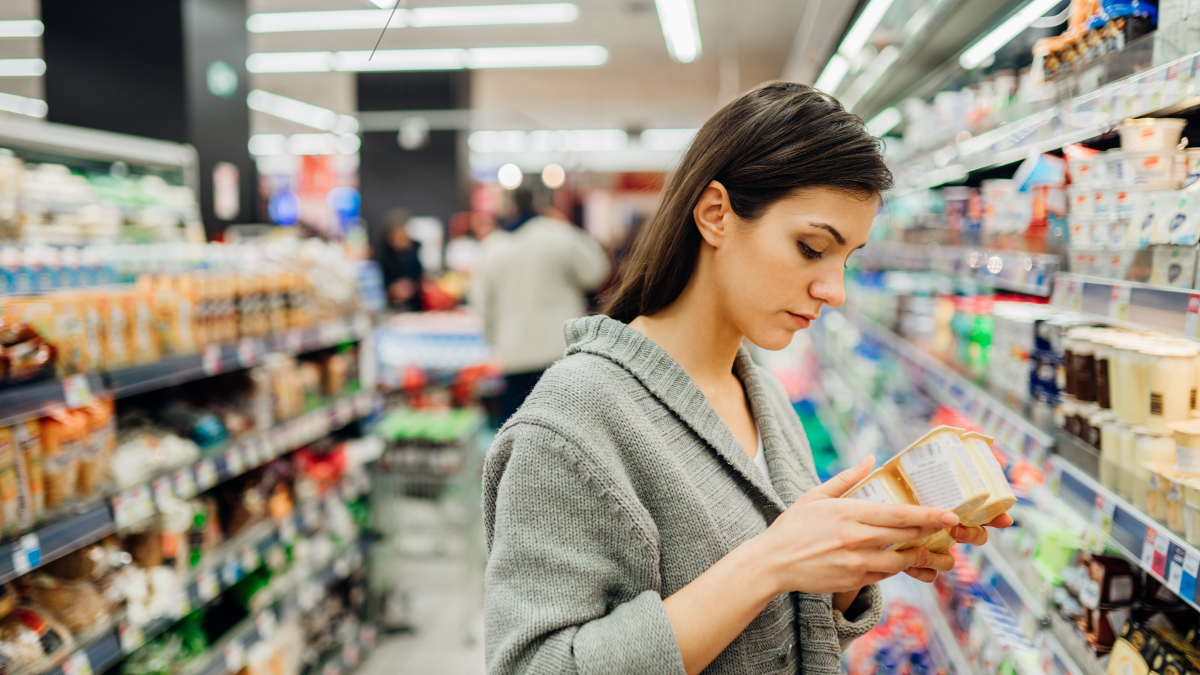 Anaemic woman in a shop checking a food product's nutritional content