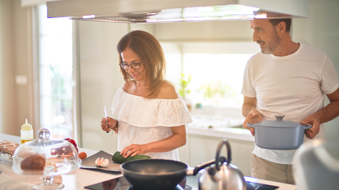 Middle age couple preparing food in their kitchen
