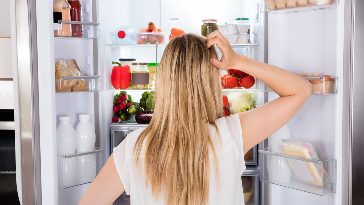 Photo of someone looking for something in the fridge