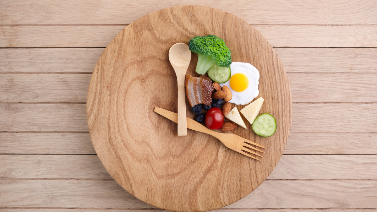Healthy food with spoon and fork resting on plate symbolizing intermittent fasting